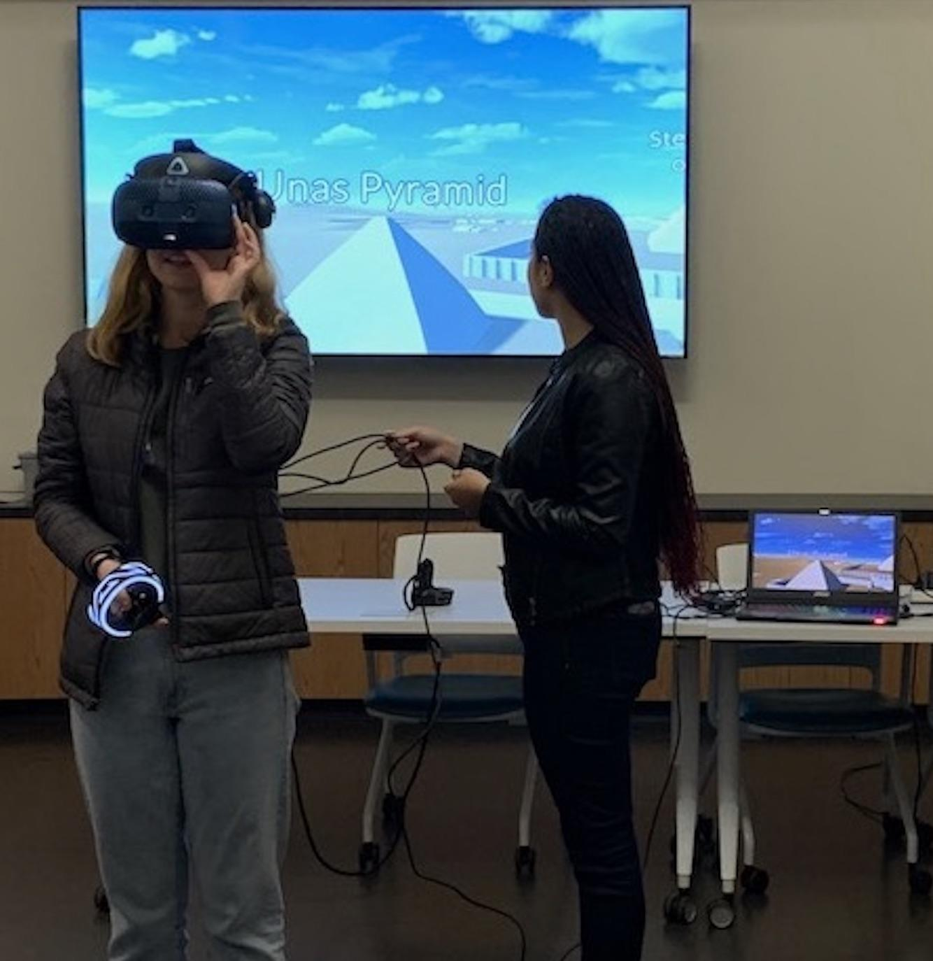 Two women testing out virtual reality equipment